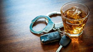 Closeup of shot glass of liquor, handcuffs, and car keys lying on a table.