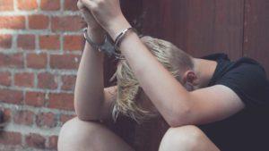 A teenage boy in handcuffs.